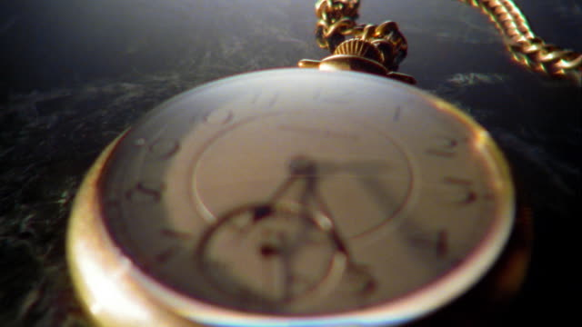 rack focus close up gold pocket watch with seconds hand moving clockwise - 懐中時計点の映像素材/bロール