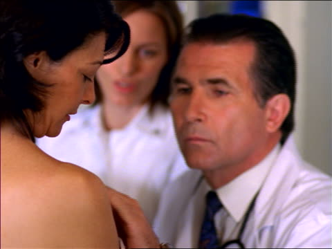 rack focus close up middle-aged male doctor examining breast of female patient / nurse in background - booby stock videos & royalty-free footage