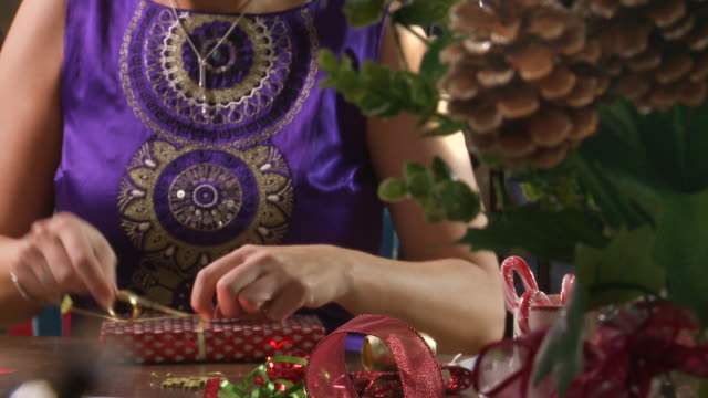 rack focus close up of festive woman wrapping presents - christmas wrapping paper stock videos & royalty-free footage