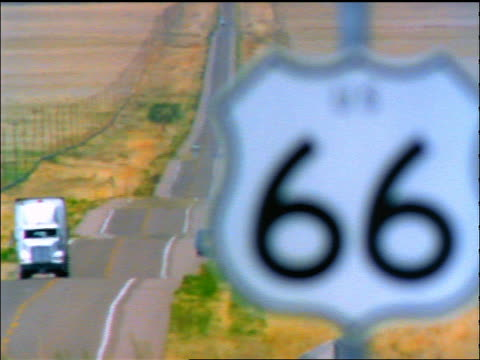 vidéos et rushes de rack focus close up route 66 sign with truck on highway in background / southwest us / heat waves - route 66