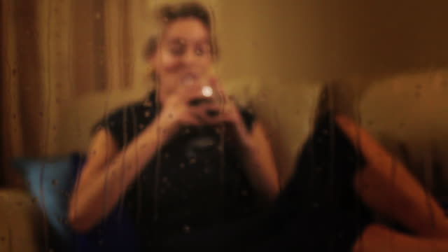 rack focus dolly shot of woman on sofa with red wine through rainy window. - three quarter length stock videos & royalty-free footage