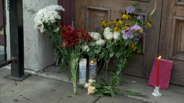 rack focus establishing shot of flowers and candles left at a makeshift memorial outside of ned peppers bar in the oregon historic district of... - dayton ohio stock videos & royalty-free footage