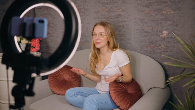 rack focus: female blogger live streaming her content showing emotions - content stock-videos und b-roll-filmmaterial