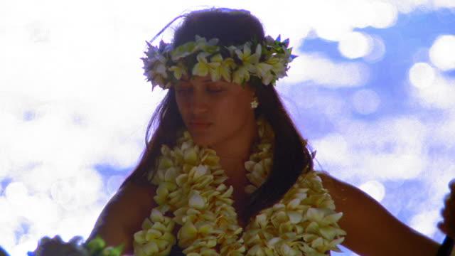 vídeos y material grabado en eventos de stock de ms rack focus female hula dancer in lei doing arm movements / ocean in background / hawaii - guirnalda