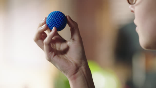 Rack focus from 3D printer in action to female engineer holding three-dimensional model ball in hand.