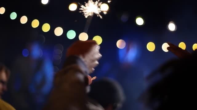 vídeos y material grabado en eventos de stock de rack focus from audience sparklers to lead singer at concert - actuación espectáculo