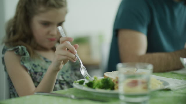 rack focus from glass of water to pouting girl playing with food / lehi, utah, united states - broccoli stock videos & royalty-free footage
