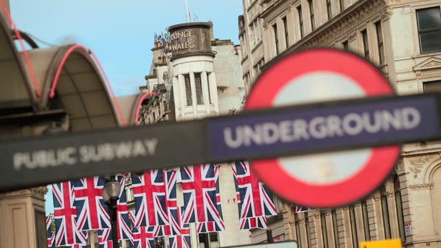 rack-fokus vom londoner u-bahn-schild bis zu reihen von hängenden union jack-flaggen. - street name sign stock-videos und b-roll-filmmaterial