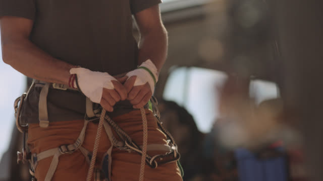 stockvideo's en b-roll-footage met rack focus from rock climber inspecting camming devices to belayer paying out rope. - kant van de weg