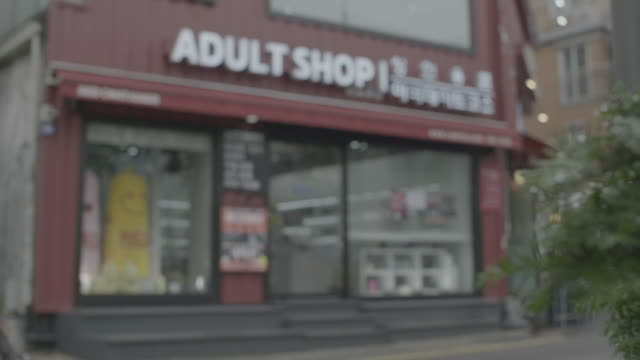 rack focus from tree to sex shop in seoul - sexual issues stock videos & royalty-free footage