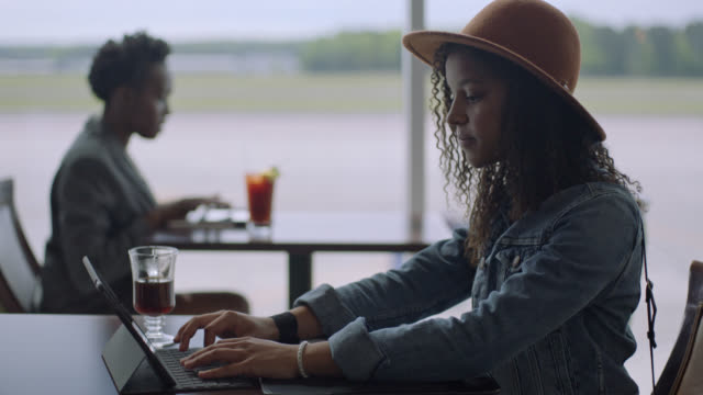 vídeos y material grabado en eventos de stock de rack focus from young female traveler to african-american businesswoman as they type on tablets at airport terminal cafe. - empleada administrativa
