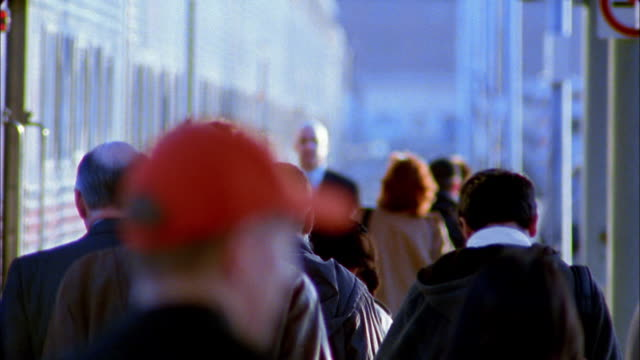 vidéos et rushes de rack focus medium shot businessman walking against traffic flow of crowd of commuters on train platform - train de banlieue