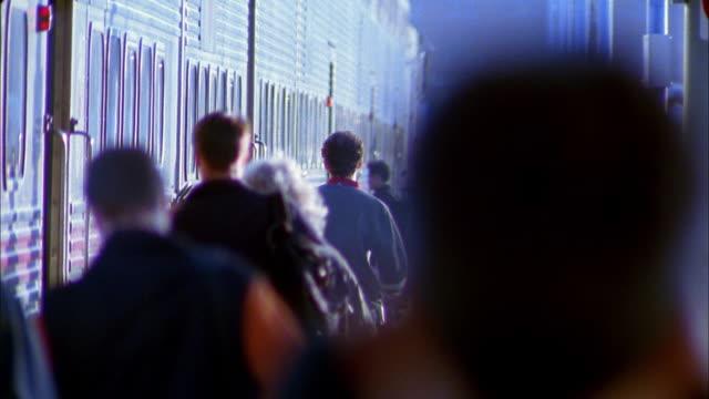 Rack focus medium shot crowd of commuters walking down train platform