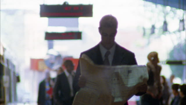 stockvideo's en b-roll-footage met rack focus medium shot tracking shot commuter unfolding newspaper on subway platform - reading