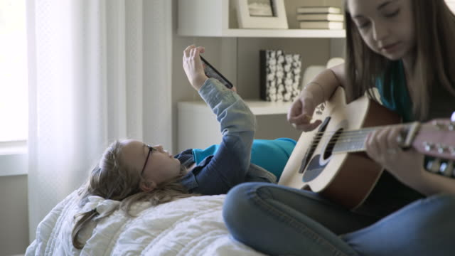 Rack focus of girl using smart phone while sister playing guitar on bed in bedroom