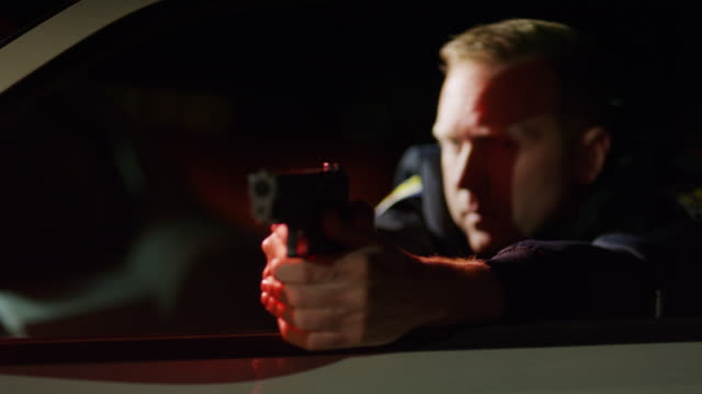 rack focus of policeman leaning on car door aiming gun at night / eagle mountain, utah, united states - aiming stock videos & royalty-free footage