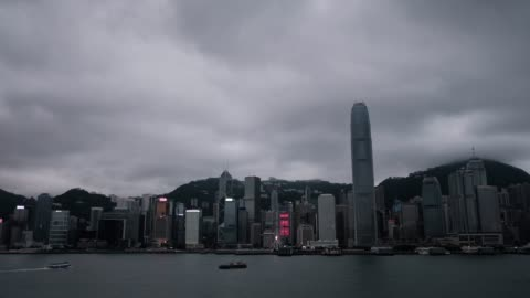 rack focus of star ferry sailing across victoria harbour with the iconic city skyline of hong kong in background - star ferry stock-videos und b-roll-filmmaterial