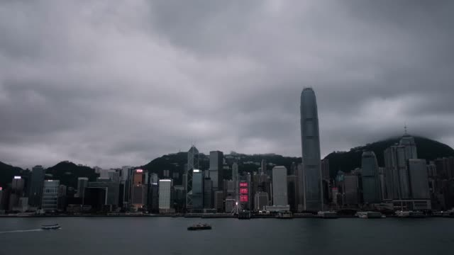 rack focus of star ferry sailing across victoria harbour with the iconic city skyline of hong kong in background - star ferry stock videos & royalty-free footage