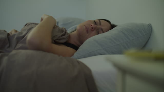 rack focus of woman in reaching for snooze button on cell phone alarm / murray, utah, united states - napping stock-videos und b-roll-filmmaterial