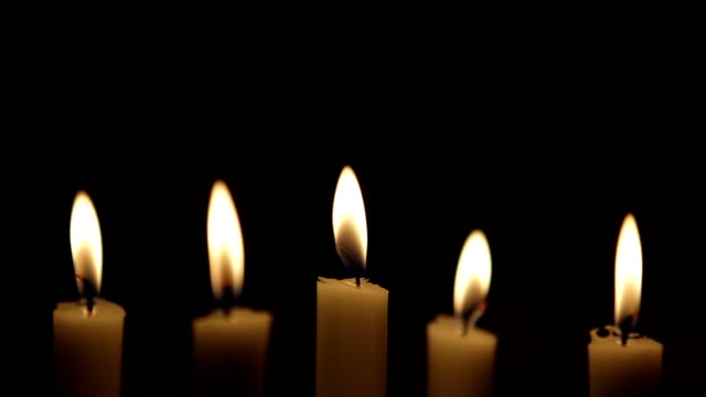 Rack focus on lit candles against black background