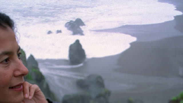Rack focus pan from high angle waves crashing on beach to close up portrait Hispanic woman smiling / California