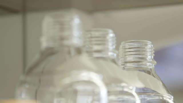 Rack focus, plastic bottles in scientific laboratory