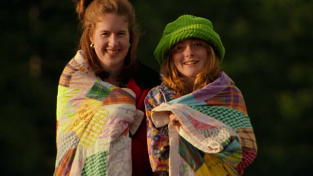 Ms Rack Focus Portrait Two Teen Girls Standing Wrapped In Quilt Laughing Smiling Outdoors Montana Stock Footage Video Getty Images