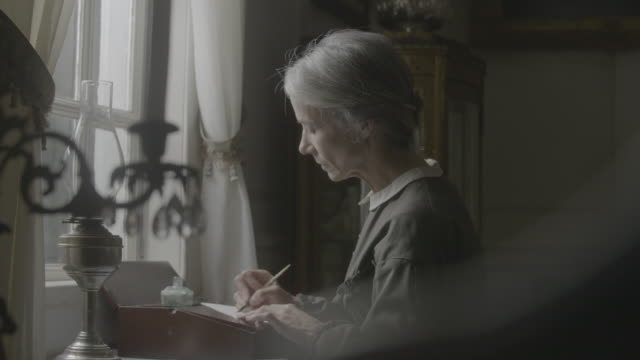 rack focus reenactment shot from a candlestick to an elderly woman writing with a dip pen and looking out of the window during the civil war era - historical reenactment 個影片檔及 b 捲影像