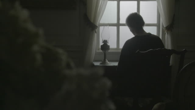 stockvideo's en b-roll-footage met rack focus reenactment shot from an elderly woman sitting in front of the window to a white bouquet of flowers during the civil war era - 18e eeuwse stijl