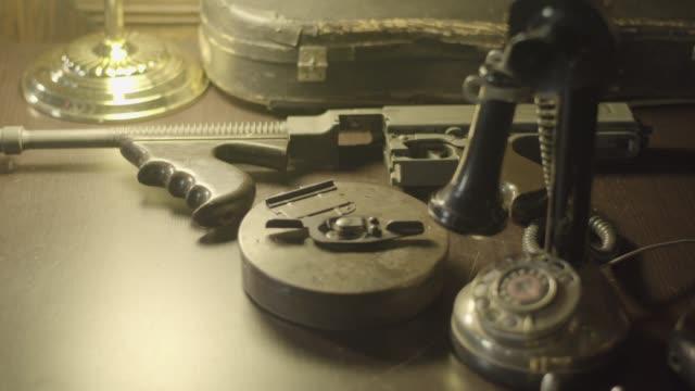 vídeos y material grabado en eventos de stock de rack focus reenactment shot of a disassembled thompson submachine gun on a desk during 1920s and 1930s - crimen organizado