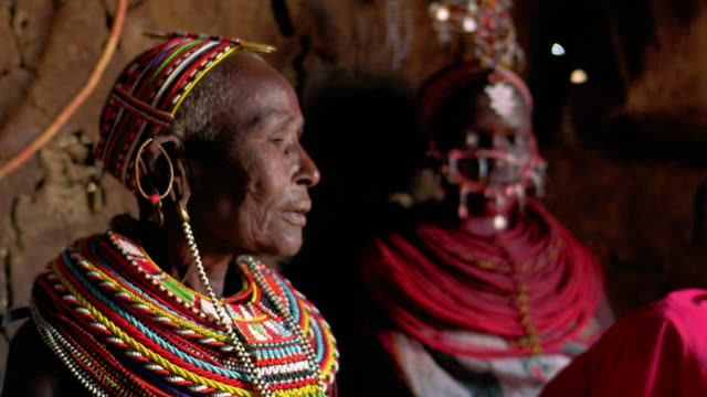 MS rack focus senior Masai tribeswoman turns + looks at camera with younger Masai woman in background / Kenya
