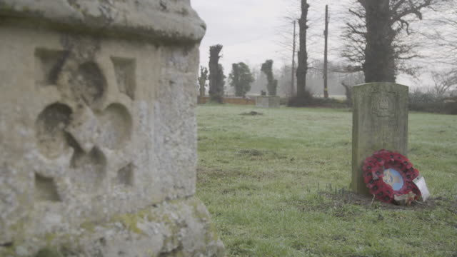 rack focus shot from a gothic style ornament to a tomb in the graveyard of the church of st mary in troston - wreath stock videos & royalty-free footage