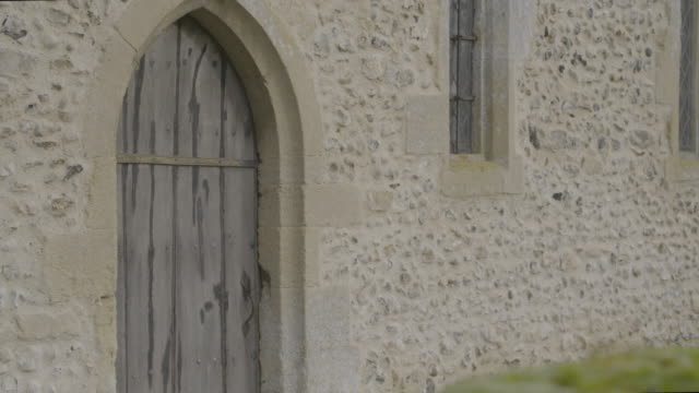 rack focus shot from a mossy stone to the wooden door of the church of st mary in troston - moss stock videos & royalty-free footage