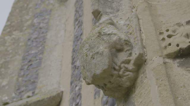 rack focus shot of a gothic style ornament on the side church of st mary in troston - moss stock videos & royalty-free footage