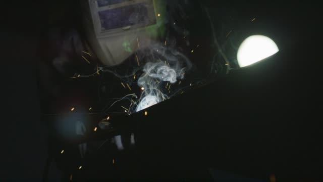 rack focus shot of a person wearing a maske und schweißen als sparks-fly - handwerker stock-videos und b-roll-filmmaterial