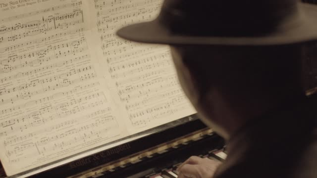 Rack focus shot of a senior African-American pianist playing the piano