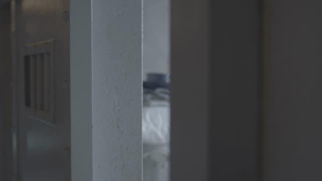 rack focus shot of a steel prison cell door closing - prisoner stock videos & royalty-free footage