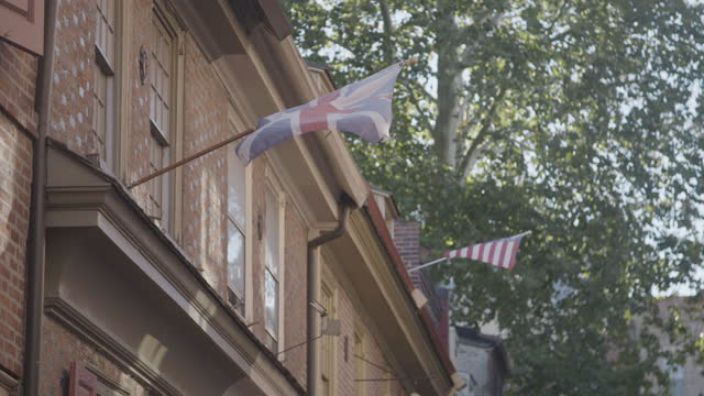 rack focus shot of a union jack and a betsy ross flag waving in the elfreths alley street - philadelphia pennsylvania stock videos & royalty-free footage