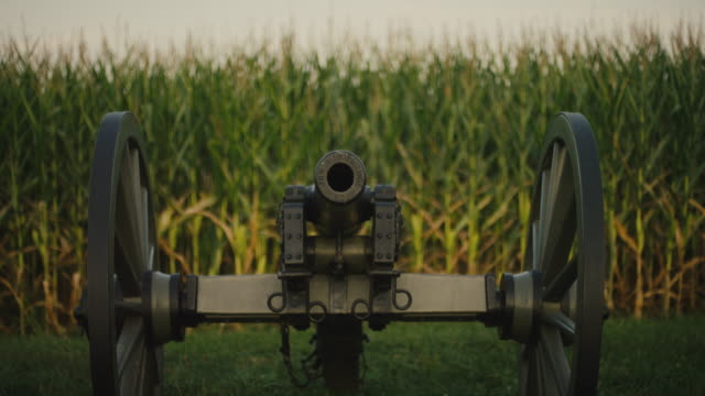rack focus shot of a us civil war cannon from gettysburg national military park, pennsylvania next to a corn field - gettysburg stock videos & royalty-free footage