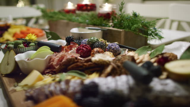 rack focus shot of an appetizer charcuterie meat/cheeseboard with various fruit, sauces, and garnishes on a table at an indoor christmas celebration/party - cheese ball stock videos and b-roll footage