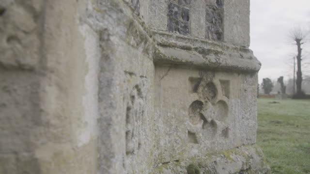 rack focus shot of gothic style ornaments on the side of the church of st mary in troston - moss stock videos & royalty-free footage
