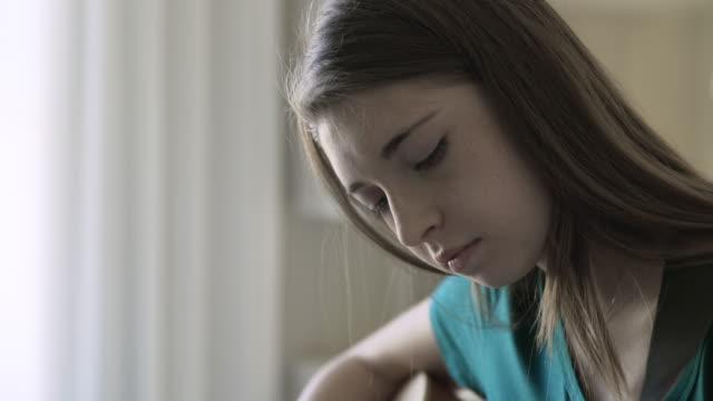 Rack focus shot of teenage girl playing guitar in bedroom