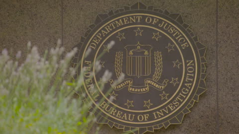 rack focus shot of the fbi sign on the wall of the j. edgar hoover fbi building - fbi stock-videos und b-roll-filmmaterial