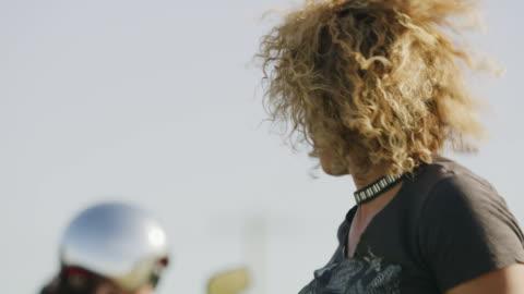 vidéos et rushes de rack focus shot of three beautiful women dismounting motorcycles / payson, utah, united states - enlever