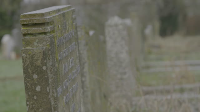 rack focus shot of tombstones in the graveyard of the church of st mary in troston - moss stock videos & royalty-free footage