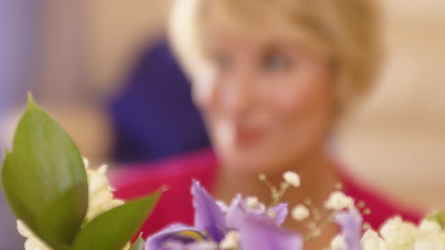 rack focus shot of woman with flower arrangement. - flower arrangement stock videos & royalty-free footage