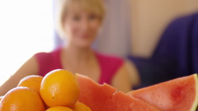 rack focus shot of woman with fruit in foreground drinking glass of orange juice. - one mature woman only stock-videos und b-roll-filmmaterial