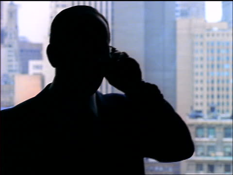 rack focus SILHOUETTE businessman in eyeglasses talking on cell phone in front of window / city in background