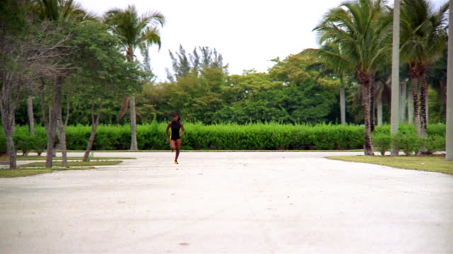 rack focus slow motion wide shot female track runner running towards camera - spandex stock videos & royalty-free footage