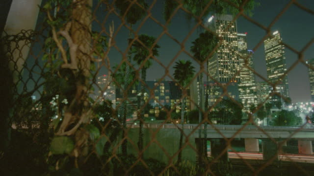 PAN rack focus time lapse traffic on highway with skyscrapers in background at night / chain link fence in foreground / Los Angeles